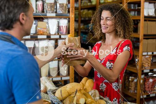 Male staff giving packed bread to woman