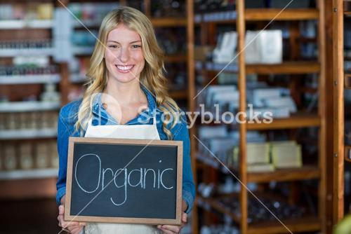 Portrait of smiling female staff holding a organic sign board