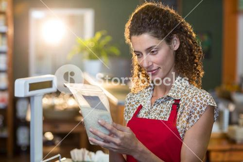 Female staff looking at a grocery item at payment counter