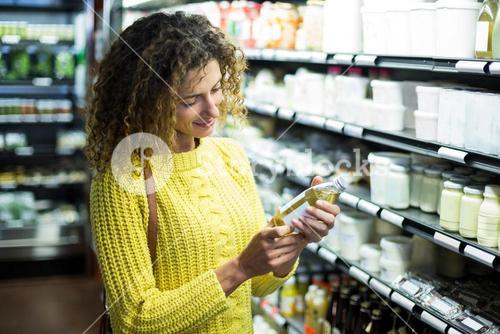 Woman selecting a bottle of oil