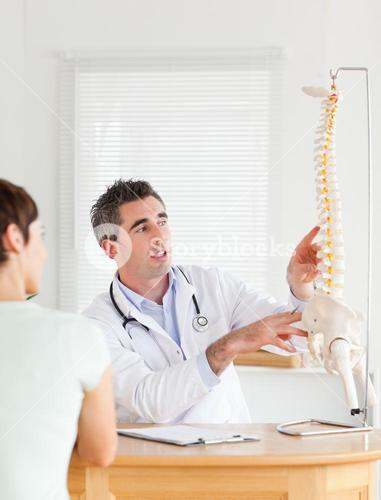 Doctor showing a female patient a part of a spine