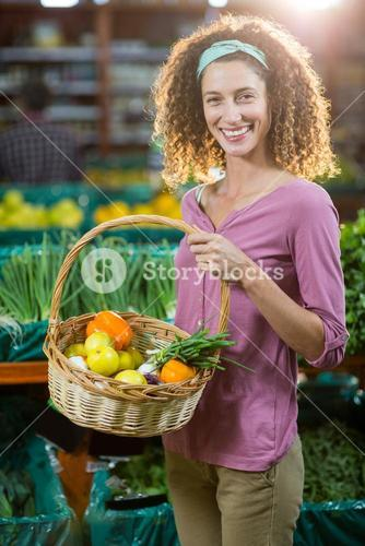 Smiling woman holding basket of vegetables in organic section