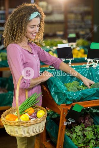 Smiling woman buying vegetables in organic section