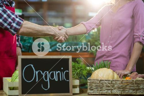 Staff shaking hand with woman in organic section