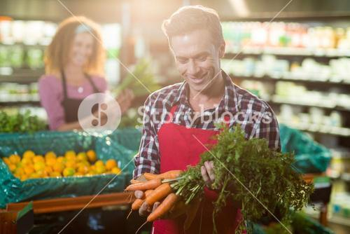 Smiling staff holding bunch of carrots in organic section