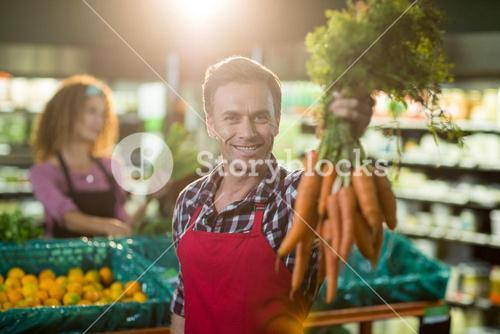 Smiling male staff holding bunch of carrots in organic section