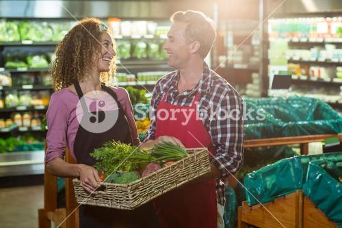 Smiling staffs holding basket of vegetable in organic section