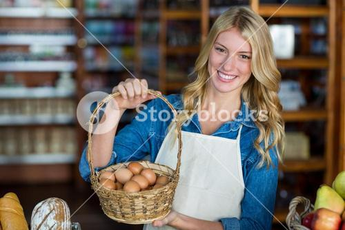 Smiling female staff holding basket of egg in supermarket