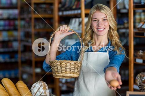 Smiling female staff holding basket and egg in super market