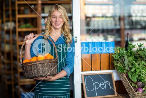 Smiling female staff holding basket of fruit in supermarket