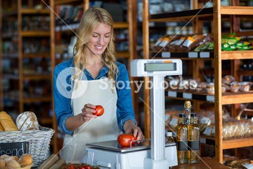 Female staff weighting vegetables on scale