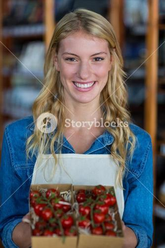 Smiling female staff holding box of cherry tomato in supermarket
