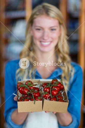 Smiling female staff holding box of cherry tomato in super market