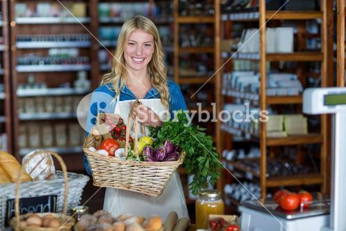 Smiling female staff holding basket of vegetables in organic section