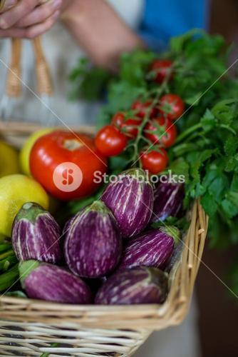Close-up of female staff holding basket of vegetables in organic section