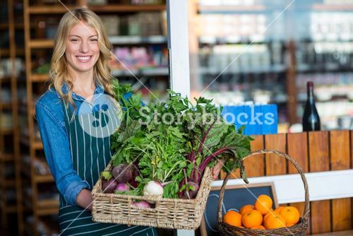 Smiling staff holding a basket of fresh vegetables in organic section