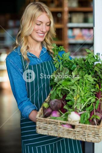 Smiling female staff holding a basket of fresh vegetables