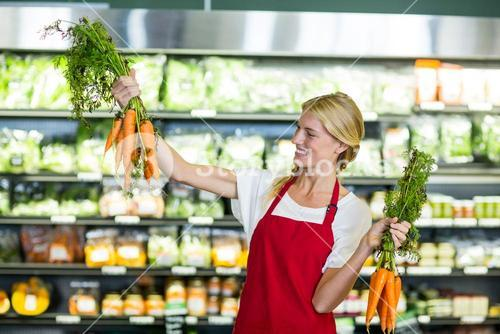 Smiling female staff holding bunch of carrots in organic section