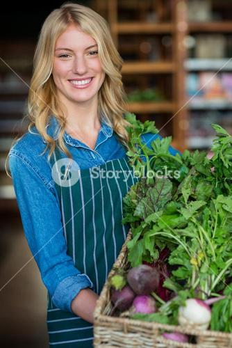 Smiling female staff holding a basket of fresh vegetables in organic section
