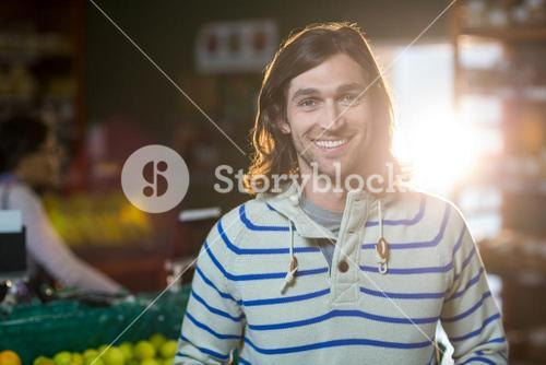 Smiling man standing in organic section