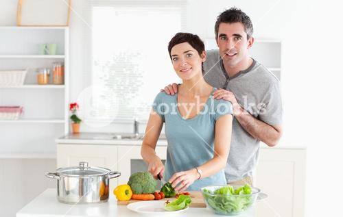 Husband massaging his wife while she is cutting vegetables