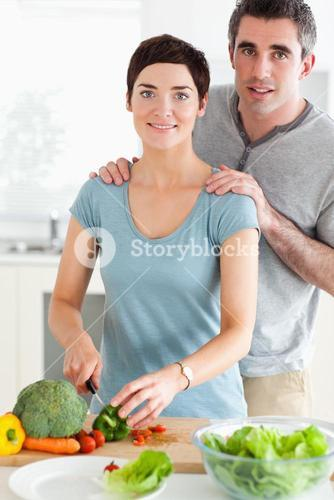 Husband massaging his wife while shes cutting vegetables