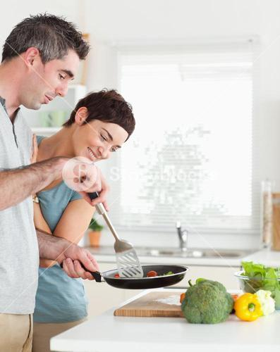 Cute Woman looking into a pan her husband is holding