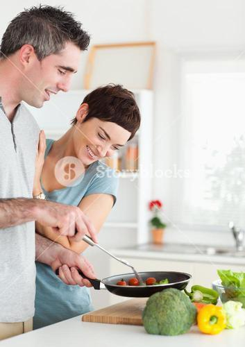 Gorgeous Woman looking into a pan her husband is holding