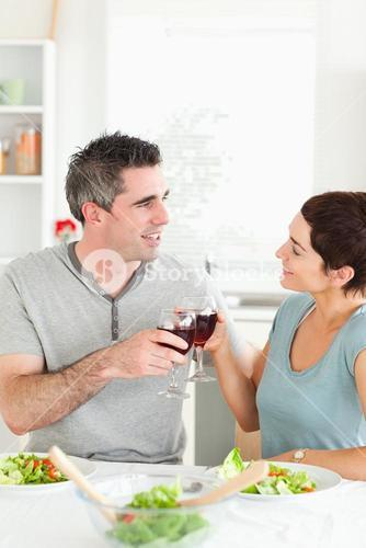 Happy couple toasting with redwine