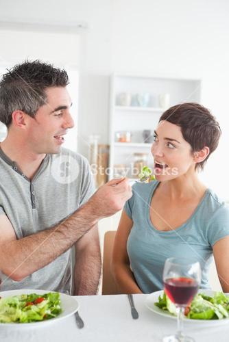 Man feeding his brunette wife