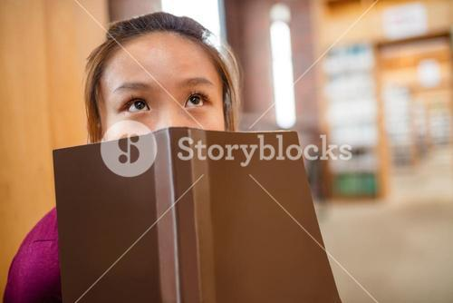 Thoughtful young woman covering her face with book