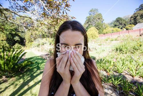 Woman blowing nose with tissue paper