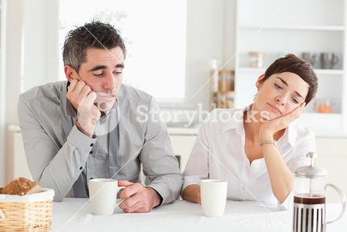 Exhausted couple drinking coffee