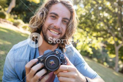 Portrait of man sitting in park with digital camera