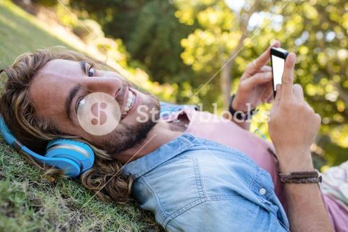 Happy man lying on grass listening to music on mobile phone