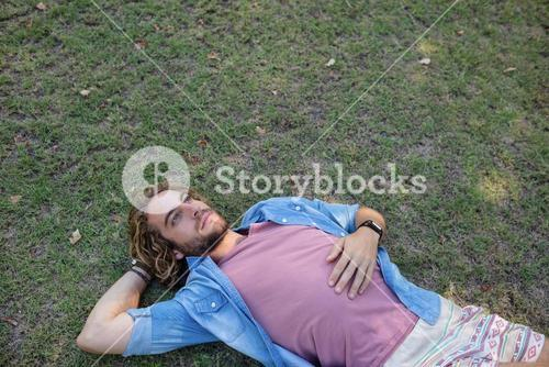 Thoughtful man lying on grass with hand behind head