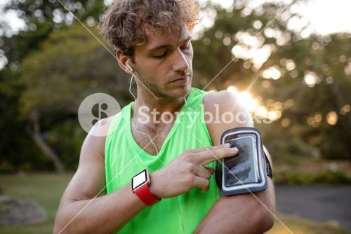 Male jogger listening to music on mobile phone