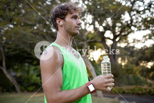 Jogger holding water bottle in park