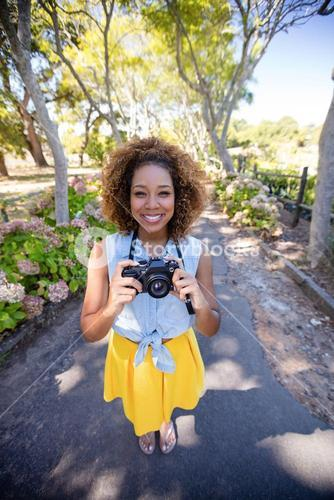 Smiling woman standing with digital camera