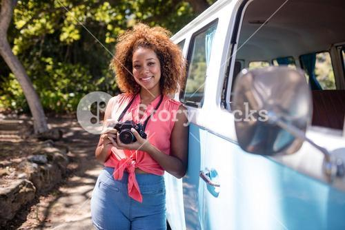 Woman leaning on campervan with camera
