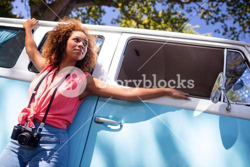 Thoughtful woman leaning on campervan with camera