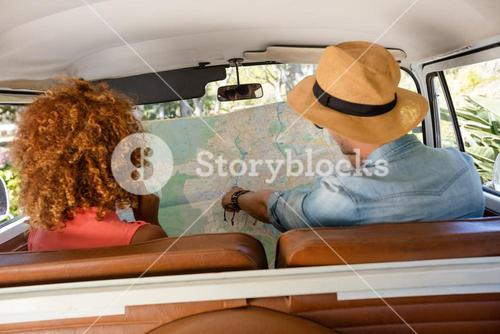 Couple looking at map in campervan