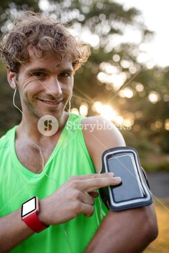 Smiling jogger listening to music from mobile phone