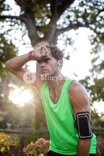 Tired man taking a break while jogging