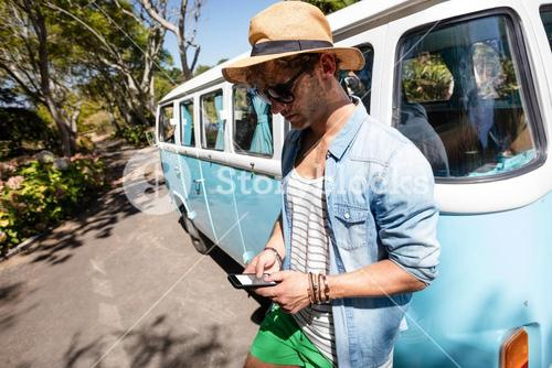 Man standing near campervan and using mobile phone