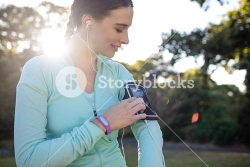Female jogger listening to music on mobile phone