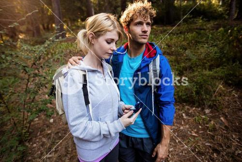 Hiking couple checking the compass