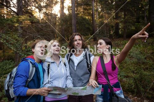 Group of friends holding a map and looking forward while hiking