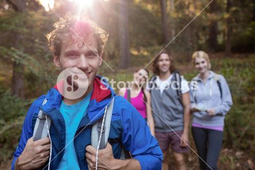 Portrait of young man hiking with his friends