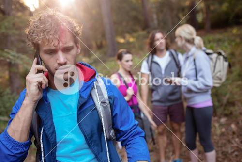 Young man talking on the phone while hiking with his friends